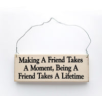 wood sign saying Making a Friend Takes a Moment, Being a Friend Takes a Lifetime