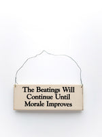 wood sign saying The Beatings Will Continue Until Moral Improves