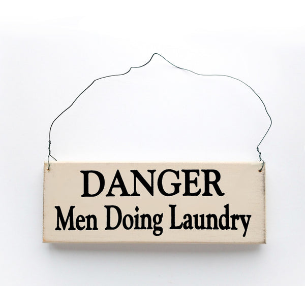 wood sign saying Danger Men Doing Laundry