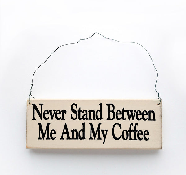 wood sign saying Never Stand Between Me and My Coffee