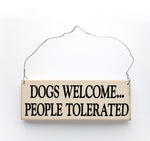 wood sign saying Dogs Welcome, People Tolerated