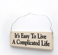 wood sign saying It's Easy To Live A Complicated Life