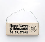 wood sign saying Happiness is Contagious, Be A Carrier