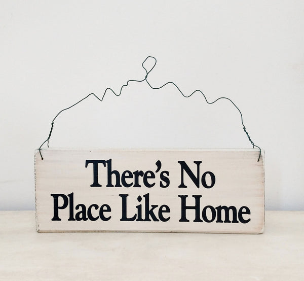 wood sign saying There's No Place Like Home