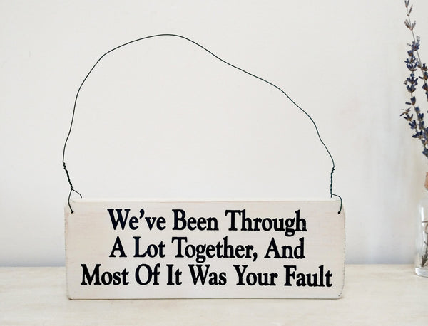wood sign saying We've Been Through a Lot Together, And Most Of It Was Your Fault