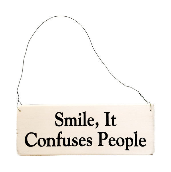 wood sign saying Smile, It Confuses People
