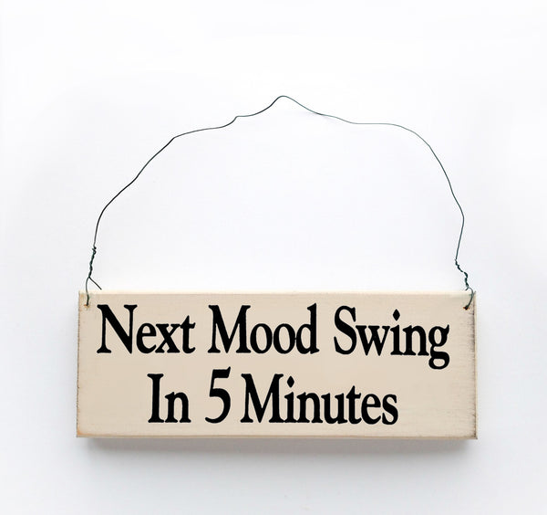 wood sign saying Next Mood swing In Five Minutes