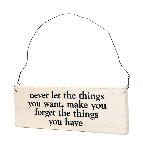 wood sign saying Never Let The Things You Want, Make You Forget The Things You Have