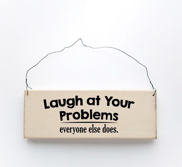 wood sign saying Laugh at Your Problems, Everyone Else Does