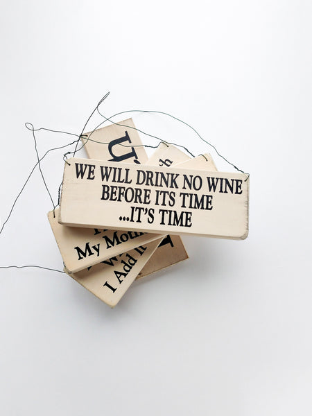 wood sign saying We Will Drink No Wine Before Its Time: It's Time