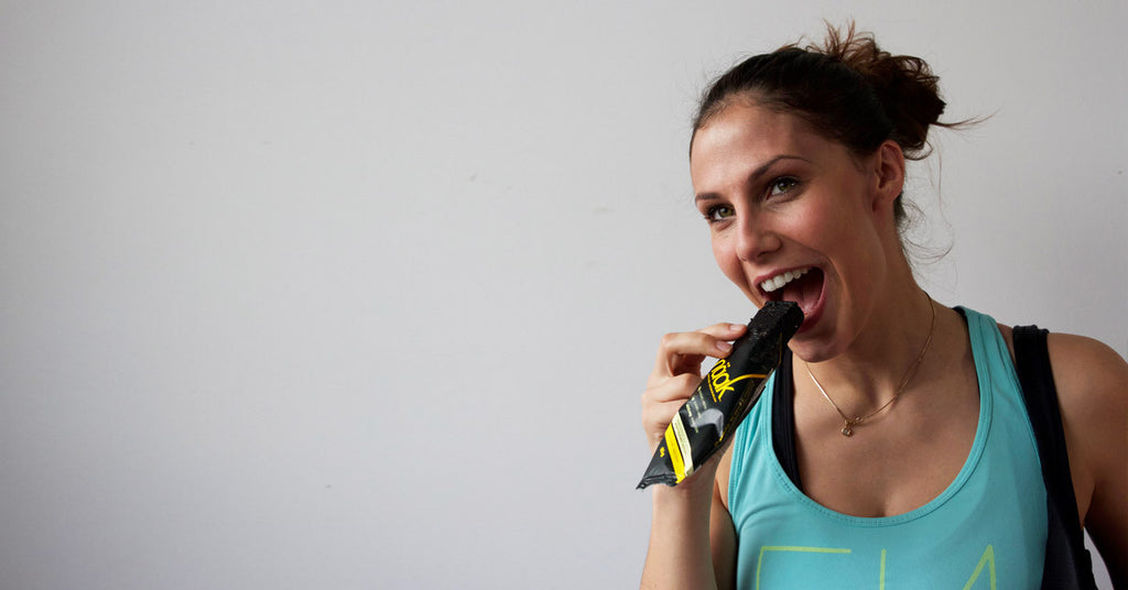 An athlete eating a Naak energy bar with cricket powder
