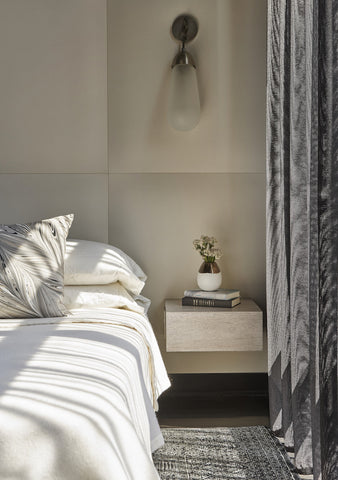 Monochromatic bedroom by Studio Gild with sconce over bedside table photographed by Mike Schwartz