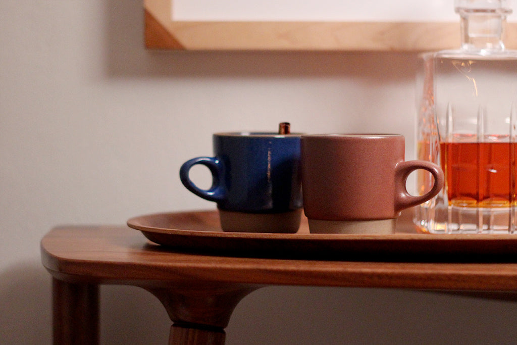 Two mugs of Hot Toddy placed on a tray on a walnut Bristol console table by Studio DUNN