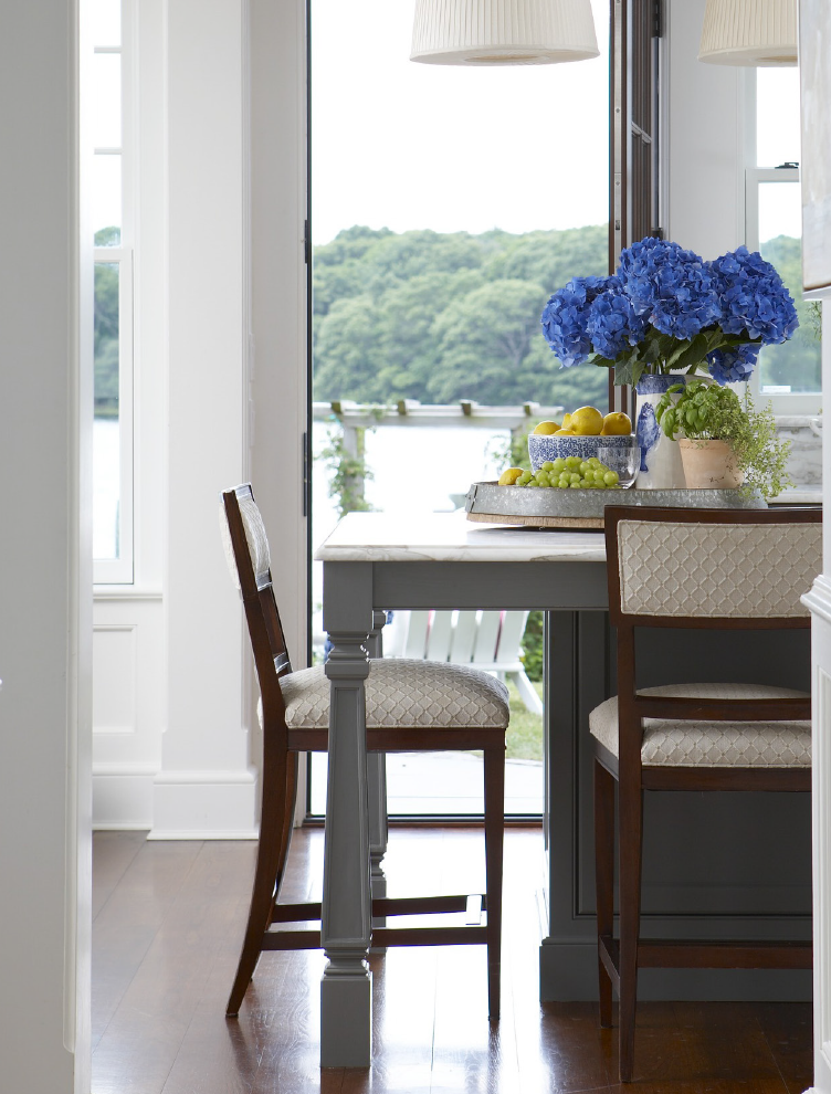 Dining chairs and table with blue flowers in front of open door overlooking a bay