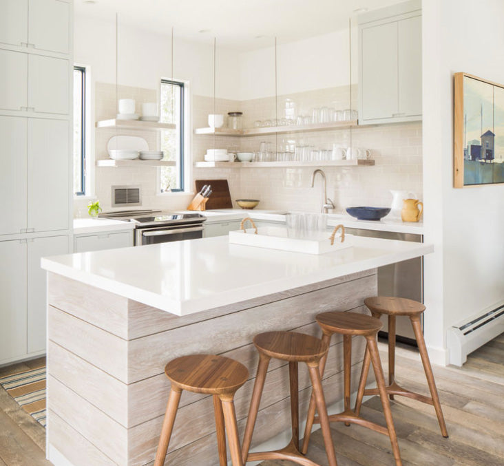 White kitchen island with walnut stools by Studio DUNN