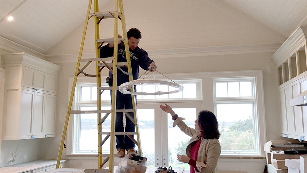 Patti Watson with electrician hanging a light fixture