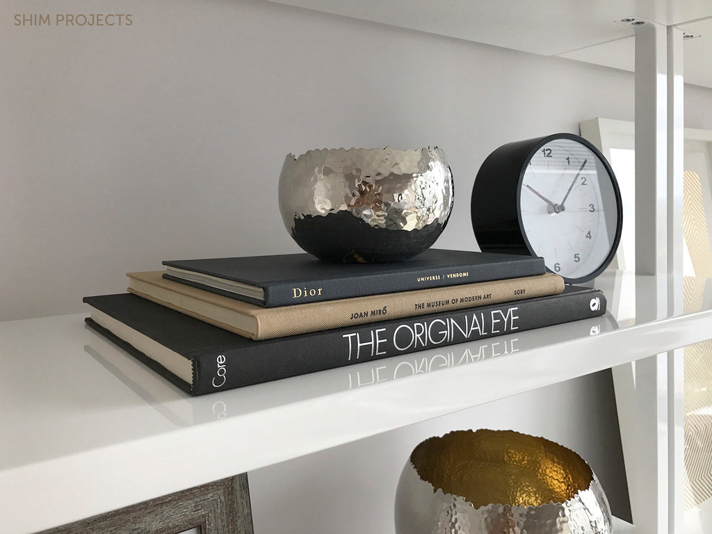 Books stacked on shelf with silver vase and clock