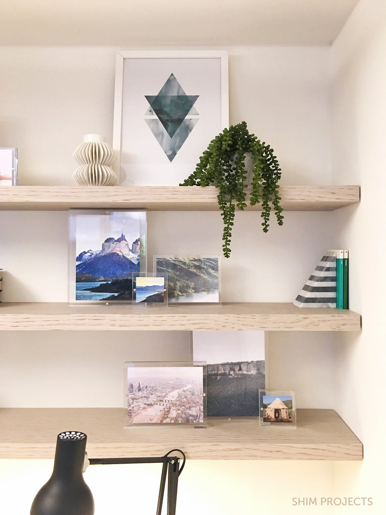 Shelving with framed art and photos and plant