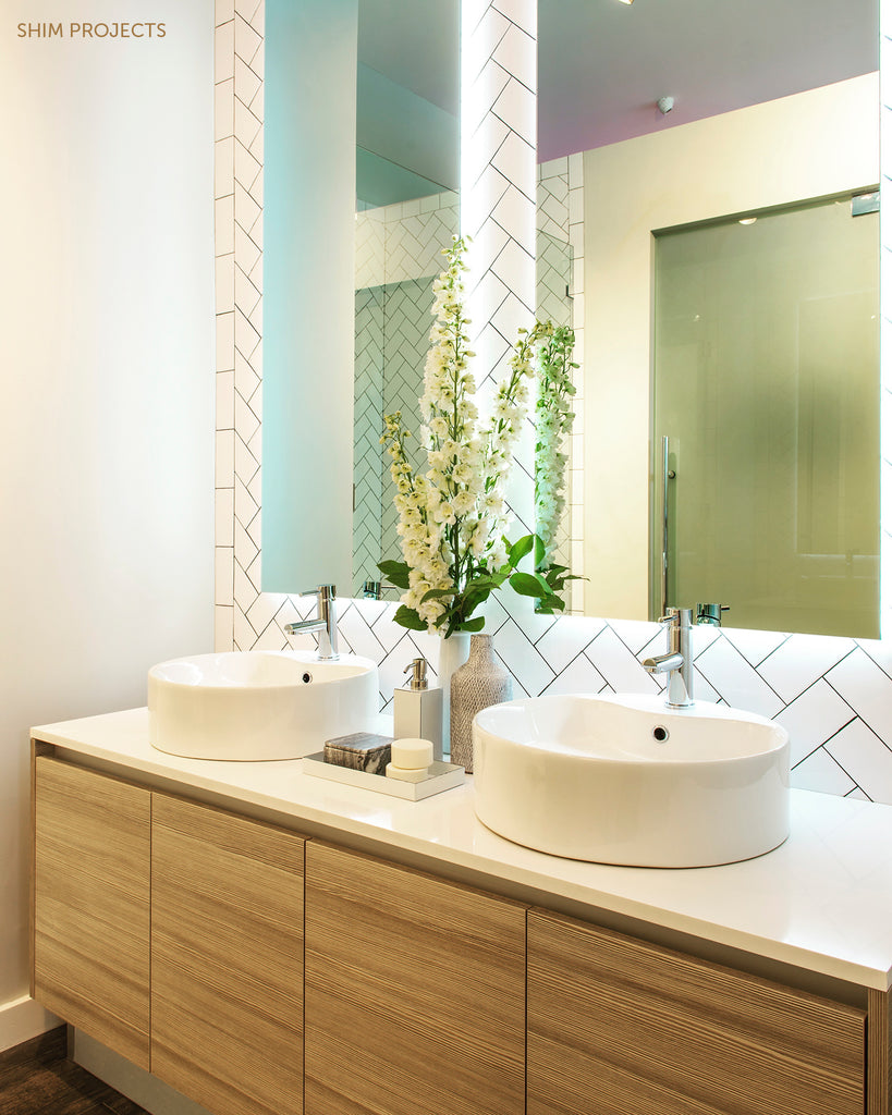 Bathroom vanity with sinks and vase with white flowers