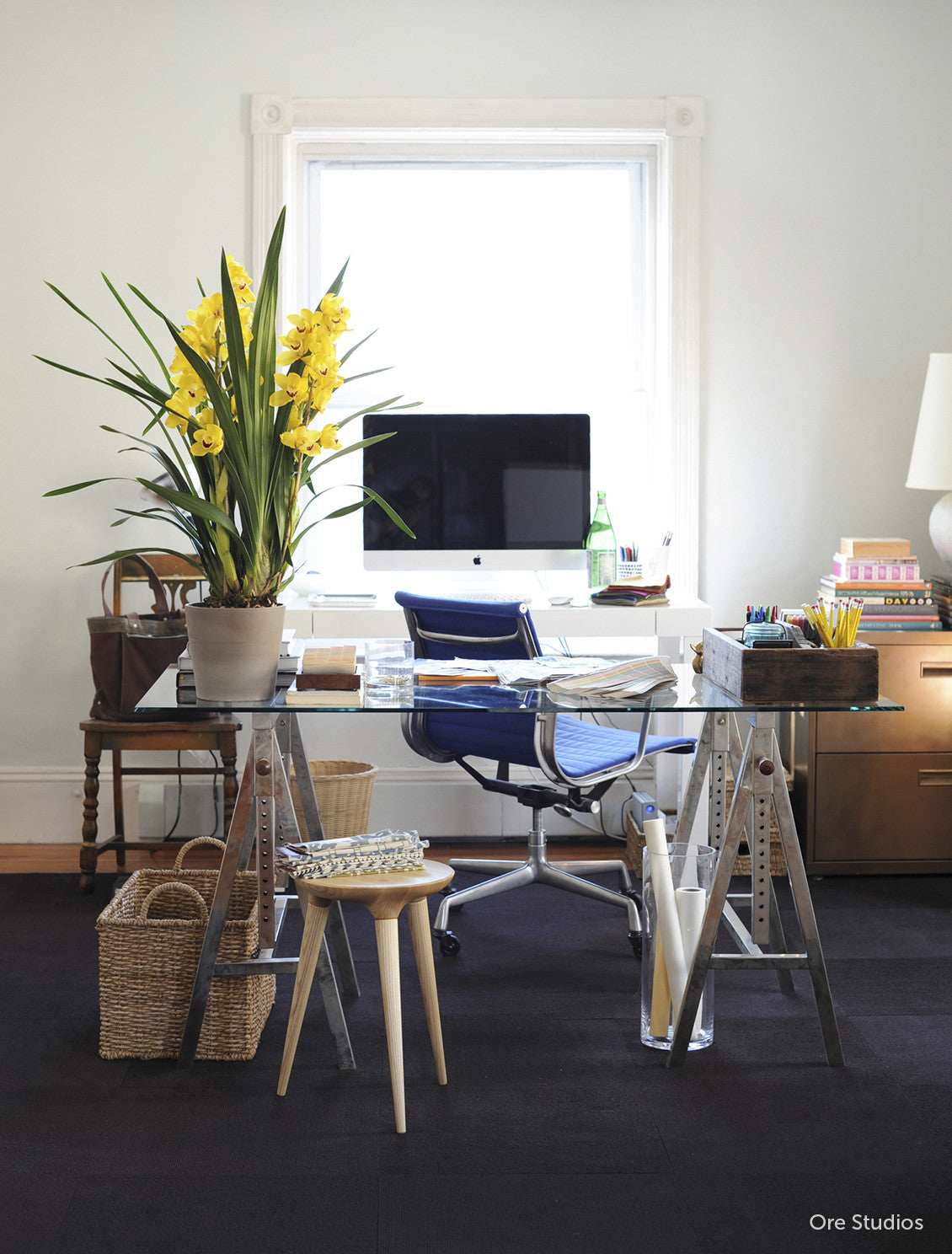 Coventry Stool by Studio DUNN in an office with a glass desktop and sawhorse legs, yellow flowers, and blue swivel chair in a space designed by Ore Studios.