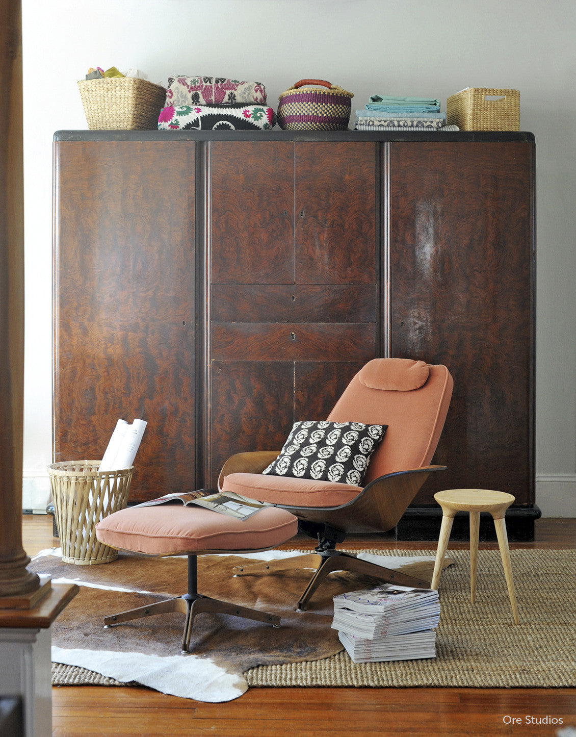 Coventry Stool by Studio DUNN as a side table next to a peach lounge chair with a hide rug below and large wooden cabinet behind in a space designed by Ore Studios