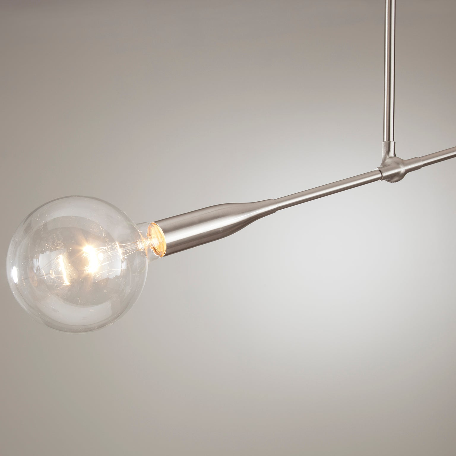 Close up view of Studio DUNN's Sorenthia Light with a globe bulb and a grey wall background