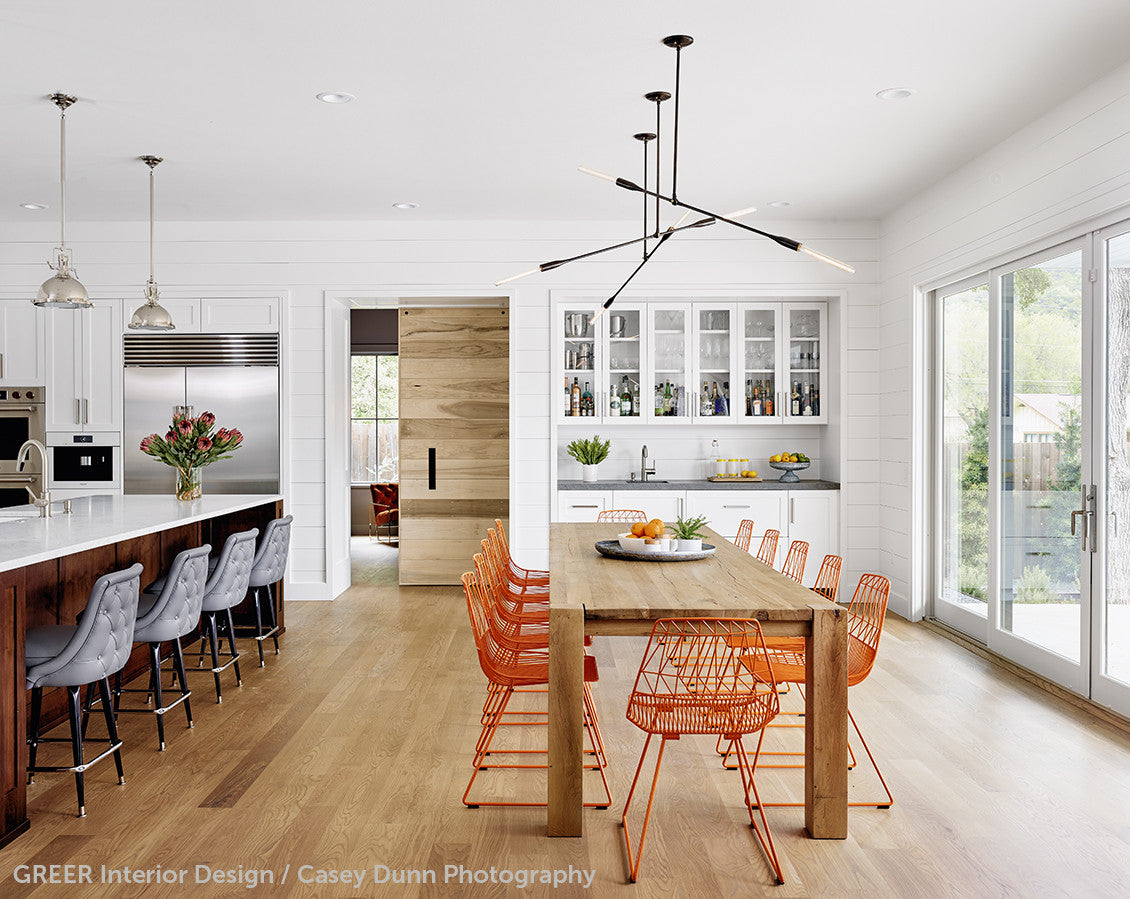 A kitchen with orange chairs at a dining table with three linear contemporary light fixtures above