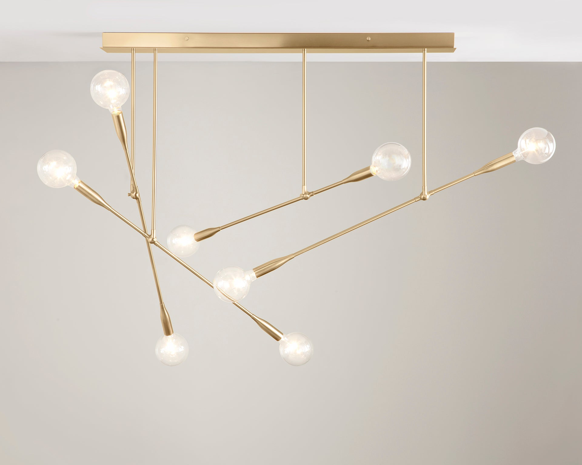 Sorenthia Quad modern chandelier in Brushed Brass with Globe Bulbs by Studio DUNN on grey background