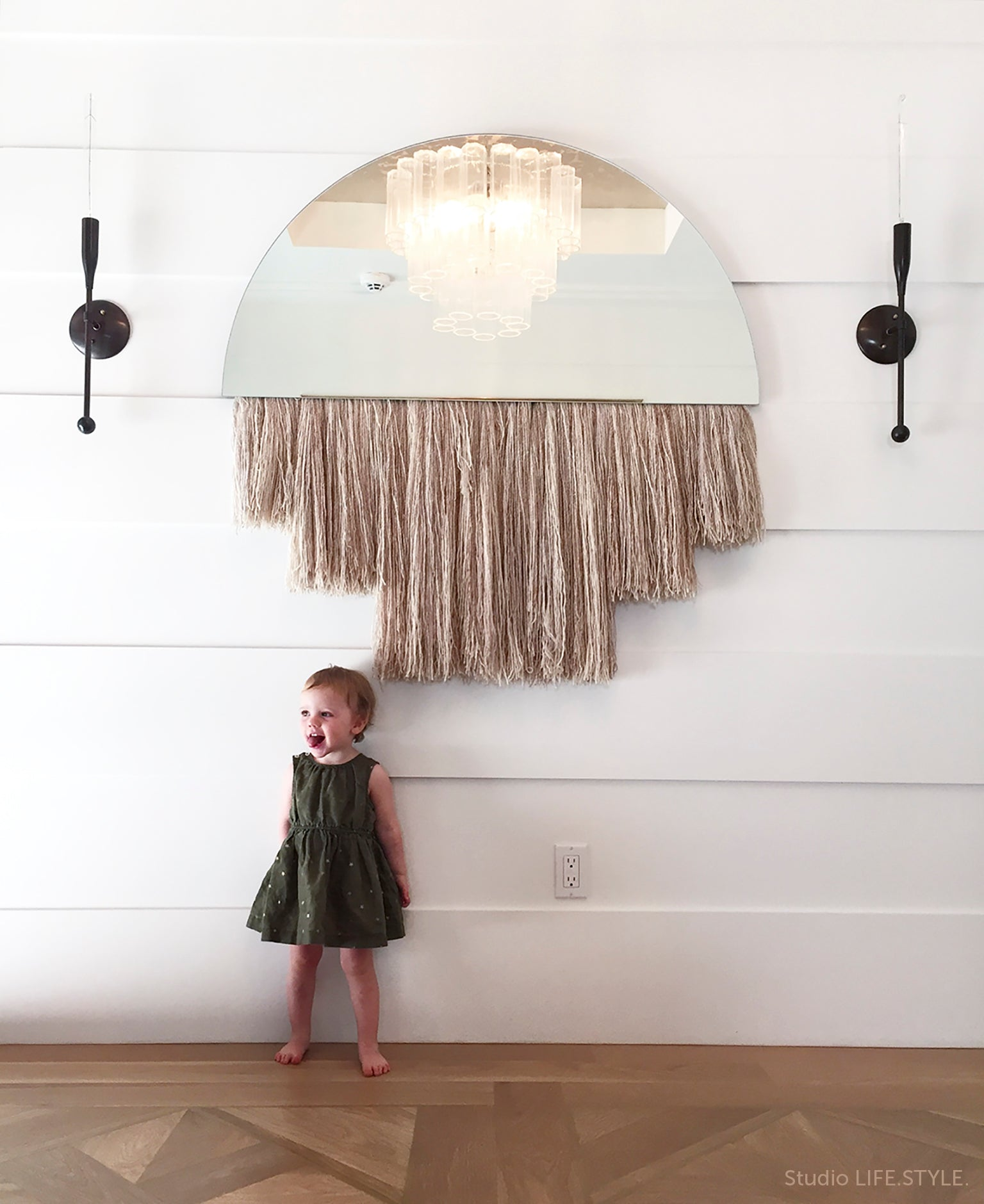 Two Sorenthia linear sconces on either side of a mirror by Ben and Aja Blanc and girl standing in a space designed by Studio LIFE.STYLE.