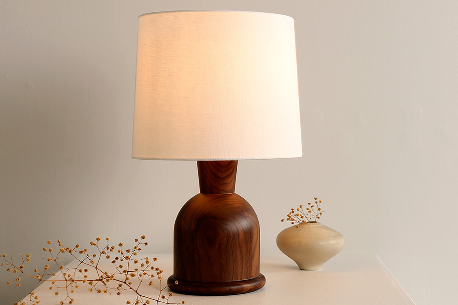 Small table lamp with hardwood lamp body and rolled linen shade