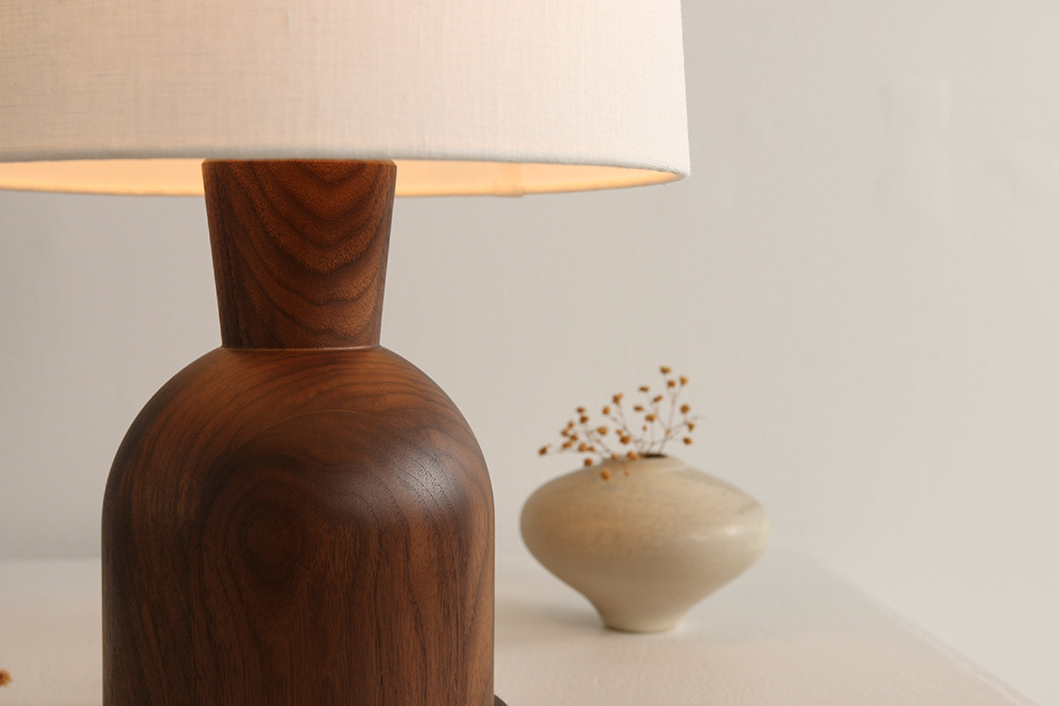 "Close up view of Beacon 18"" Table Lamp with walnut lamp body and cream linen shade by Studio DUNN"