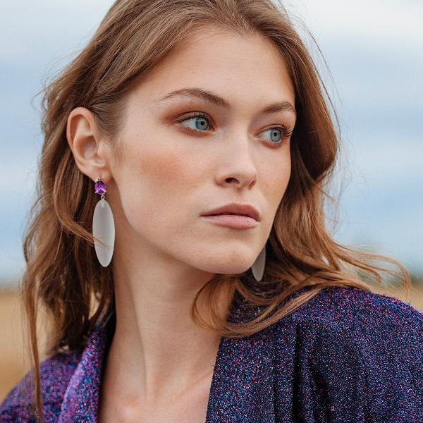 portrait, woman looking left, purple glitter jacket, large rubber earring.