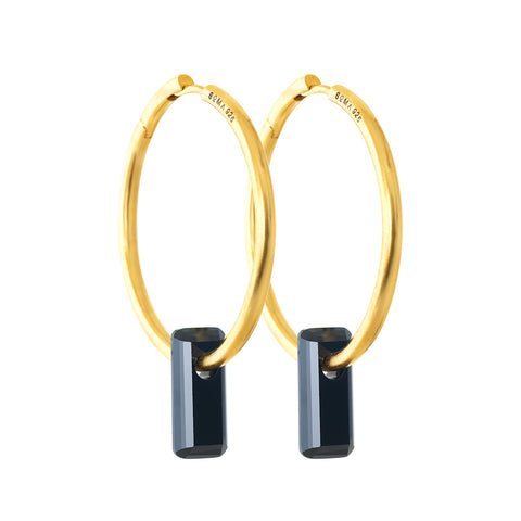 golden earrings, large hoops, black stone trough hoops, white background.
