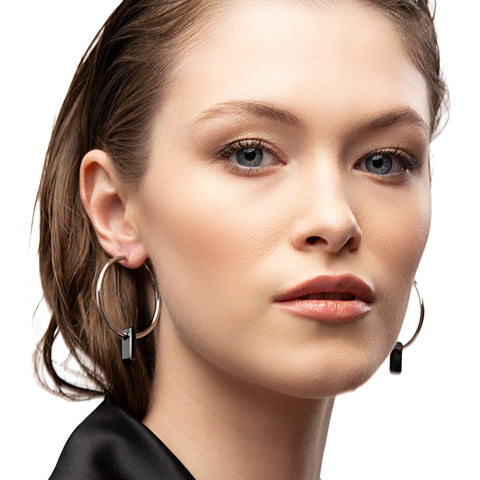 silver earrings, large hoops, black stone trough hoops, white background.