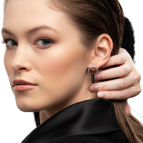 asymmetrical pair of earrings, hoops and stud, silver, big black stone, white background.