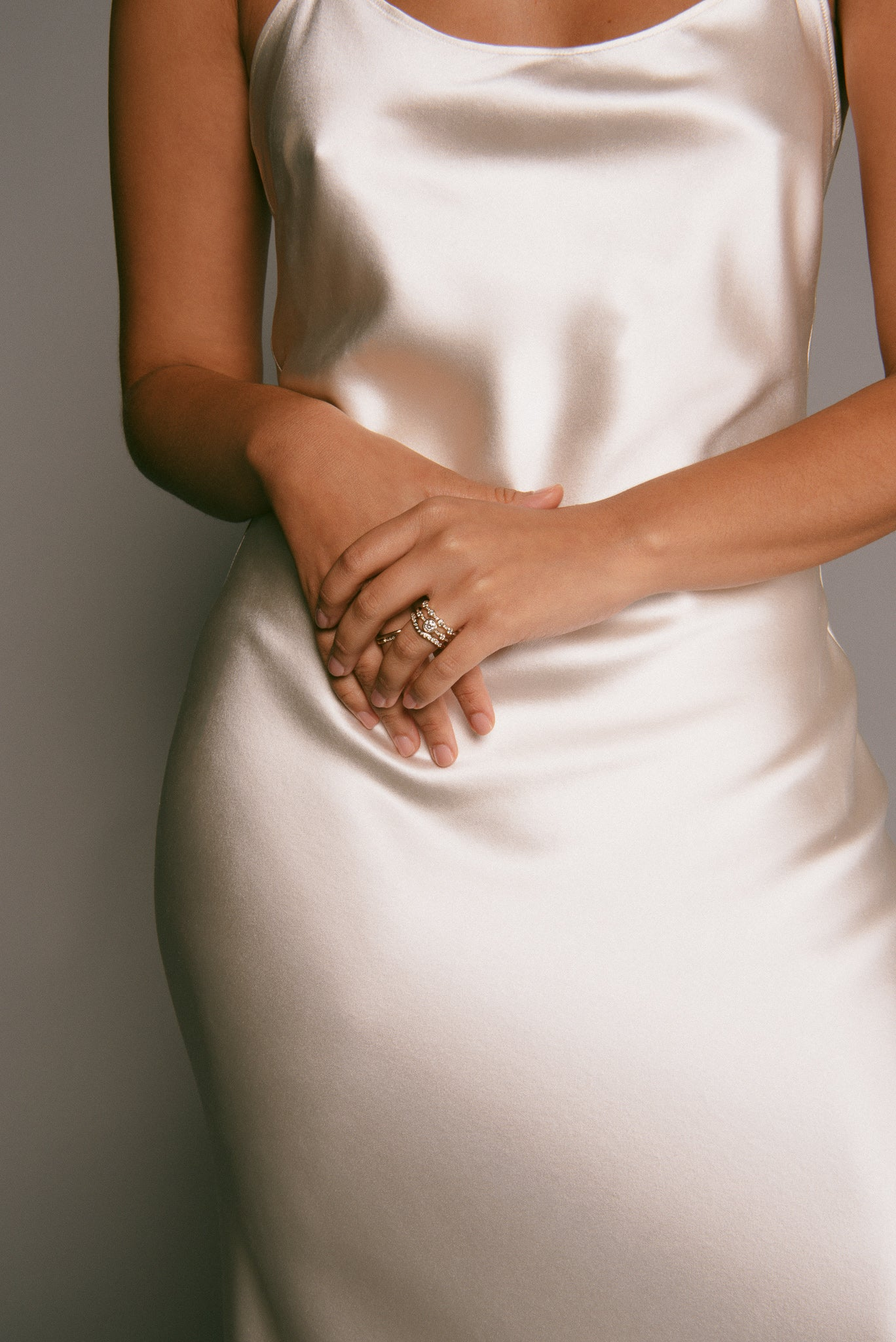 Model in a silk dress, clasping her hands, wearing three bridal-inspired rings.