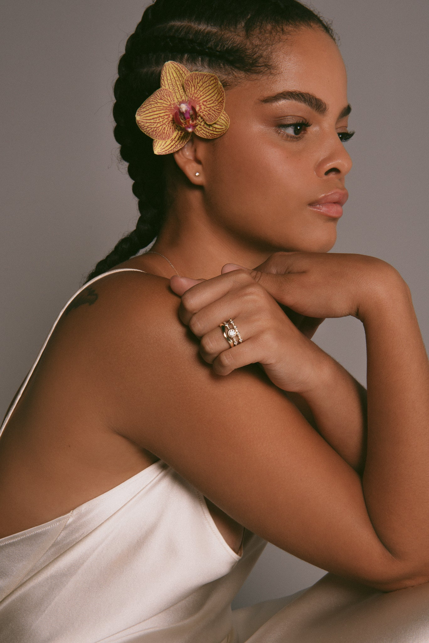 Lyl with an orchid in her hair in a white silk dress.