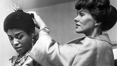 Black and white image of Vivianna Torun Bülow-Hübe fixing a silver comb to the head of singer, songwriter, actor, and activist Abbey Lincoln