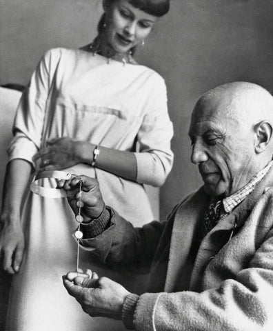A black and white photo of Vivianna Torun Bülow-Hübe standing above seated Pablo Picasso who is holding a piece of her jewelry in his hands