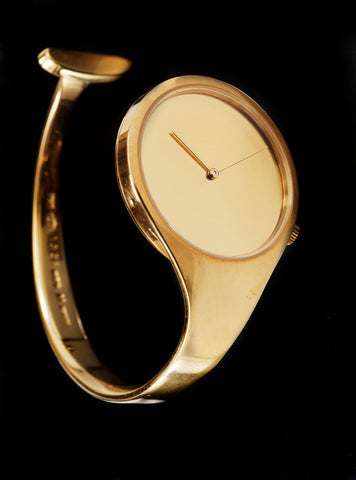 A golden wristwatch designed by Vivianna Torun Bülow-Hübe without an hour hand or numbers sitting against a black background