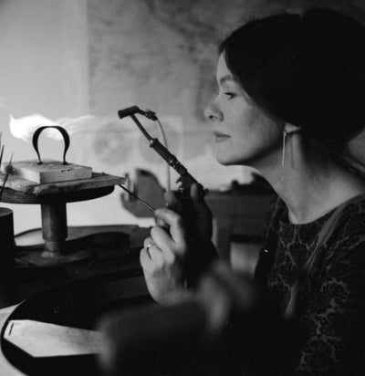 A black and white photo of Vivianna Torun Bülow-Hübe working at her jewelers bench with a blowtorch