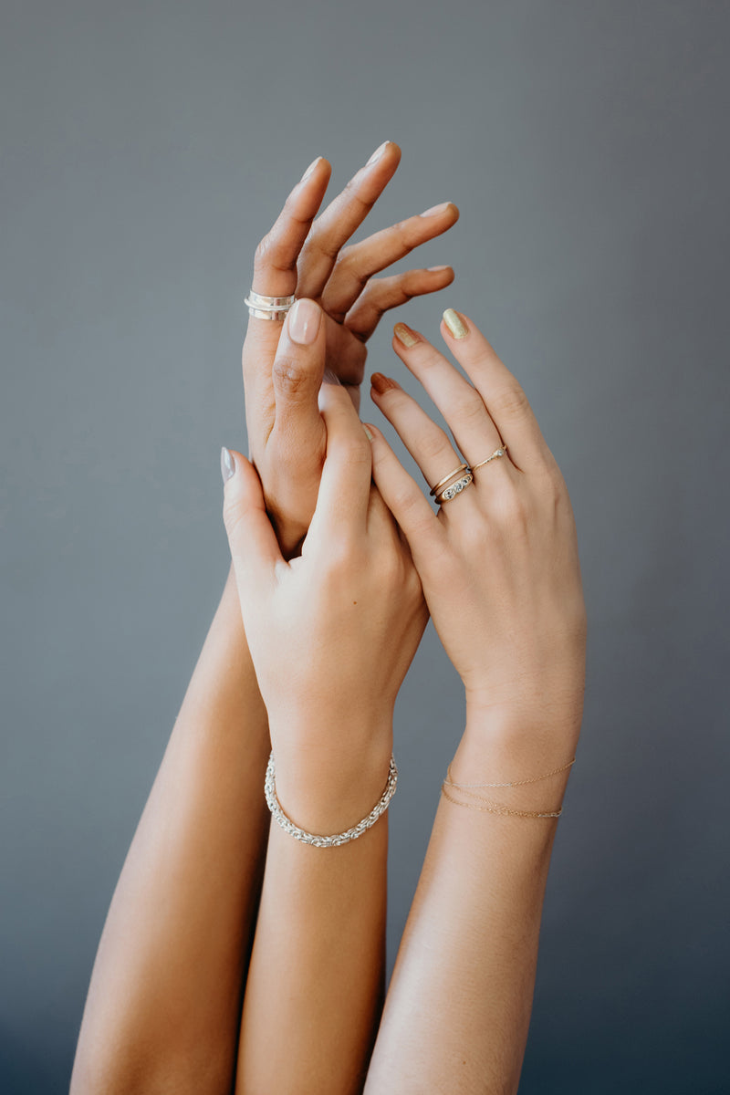 Three different hands reaching upwards together modeling various yellow gold and white gold ring styles including the Ageku band and silver Enzo bracelet against a grey back drop