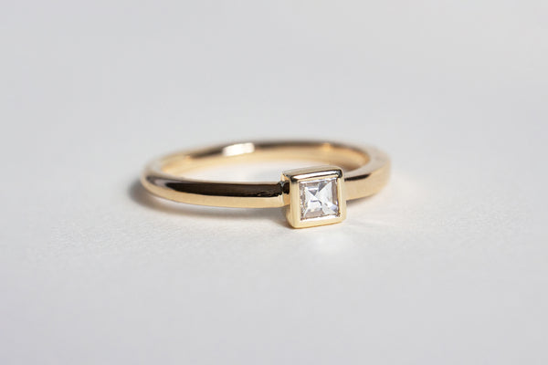 A yellow gold band that is rounded on one end and transitions to be squared on the other with a square framed white diamond setting