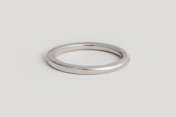 A white gold band that is rounded on one end and transitions to be squared on the other