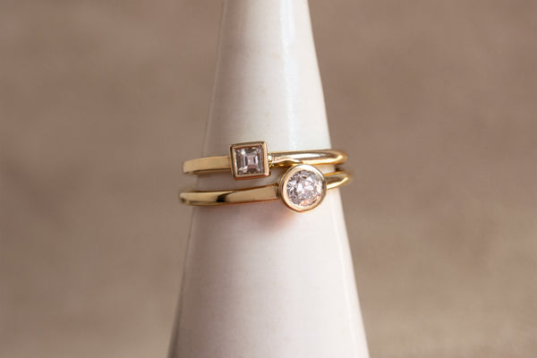 A closeup view of the Carré square cut and round old European yellow gold Ageku rings