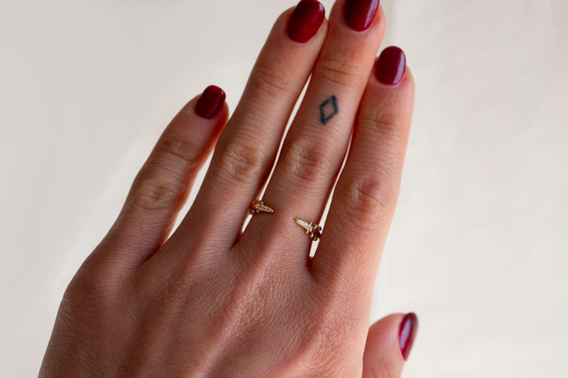 The Kuli Ring on a model's middle finger. A 14k yellow gold ring that is open in the center and has tapered ends. The ends taper to points, and there are three white diamonds set into each point. Three sets of beads sit just beyond the diamonds.