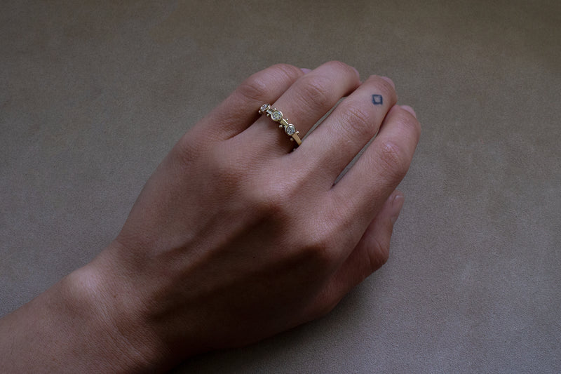 A hand wearing the Koemi ring on the ring finger against a tan background