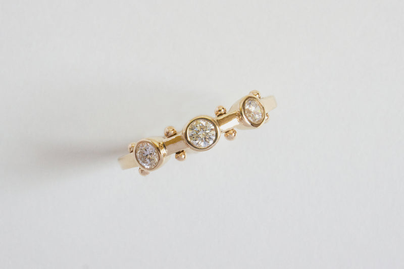 A closeup top view of yellow gold band with three small white diamond settings and two small yellow gold balls between each diamond setting along the sides of the band
