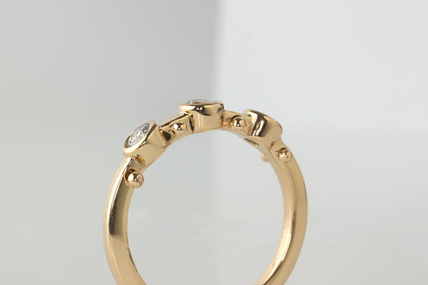 A closeup side view of yellow gold band with three small white diamond settings and two small yellow gold balls between each diamond setting along the sides of the band