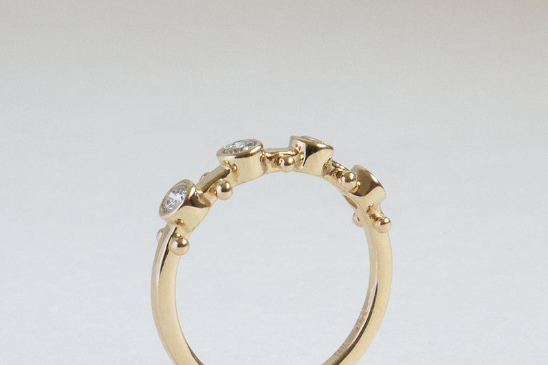 A Closeup side view of a yellow gold band with four small white diamond settings and two small yellow gold balls between each diamond setting along the sides of the band
